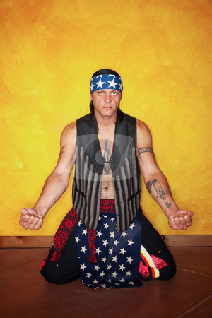 Kneeling Native American man stock photo, Kneeling Native American man with tattoos and vest by Scott Griessel