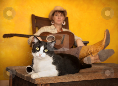 Pretty Western Woman with Guitar and cat stock photo, Pretty western woman in antique rocking chair with guitar and cat by Scott Griessel