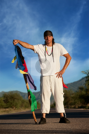 Man in the middle of a road with flags stock photo, Native American man in the middle of a road with flags representing four directions by Scott Griessel