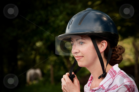 Costa Rican tourist putting on equestrian helmet stock photo, Female Costa Rican tourist putting on equestrian helmet by Scott Griessel