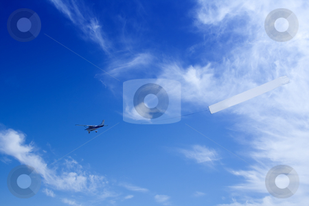 Plain stock photo, Small airplane pulling a blank sign for advertisements by GPimages