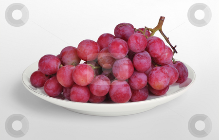 Grapes on a plate stock photo, Luscious purple geapes on an offwhite plate by Boaz Yiftach