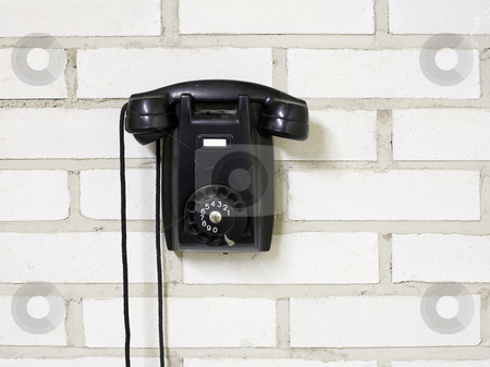 Telephone stock photo, Black bakelite telephone on a brick wall. by Stocksnapper