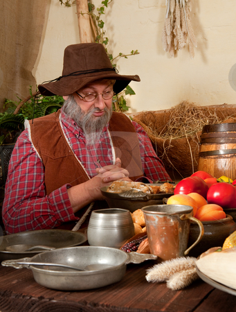 First Thanksgiving prayer stock photo, Reenactment scene of the first Thanksgiving Dinner in Plymouth in 1621 with a Pilgrim family and a Wampanoag Indian by Anneke