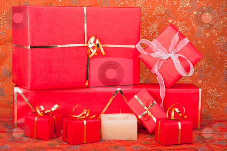 Gift Boxes and Candle stock photo, Red and gold gift boxes with a candle on a Xmas background by Timothy Hodgkinson