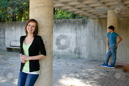 Smiling Teen Girl stock photo, A female teenager is posing by a stone pillar with her boyfriend in the background. by Richard Nelson