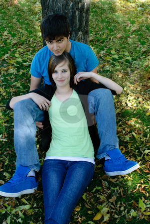 Teenage Couple Resting stock photo, A teenage couple is resting by a tree in the fall with leaves on the ground by Richard Nelson
