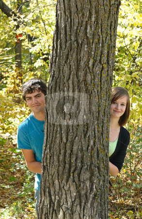 Teen Couple stock photo, A teen couple peeking out from behind a tree in the forest by Richard Nelson