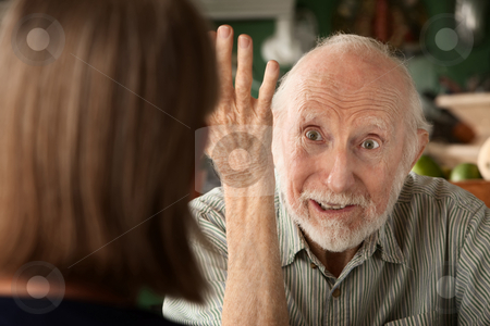 Senior couple at home focusing on angry man stock photo, Senior couple at home in kitchen focusing on angry man by Scott Griessel