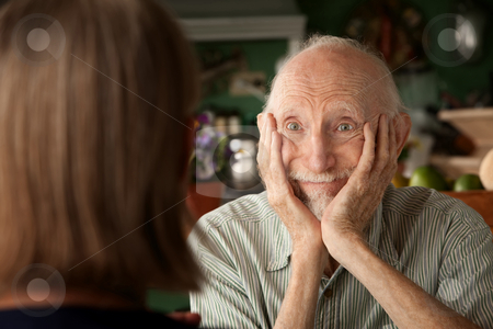 Senior couple at home focusing on man stock photo, Senior couple at home in kitchen focusing on man by Scott Griessel