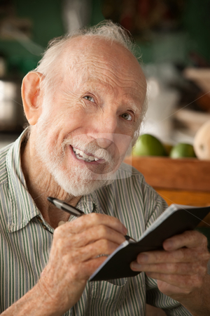 Senior man with checkbook stock photo, Senior man at home with checkbook by Scott Griessel