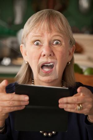Senior woman with checkbook stock photo, Senior woman at home with checkbook by Scott Griessel