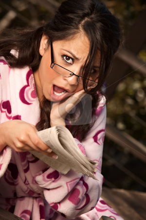 Pretty Hispanic Woman in Bathrobe with Newspaper stock photo, Pretty Hispanic Woman in Bathrobe Sitting Outdoors Reacts to Newspaper by Scott Griessel