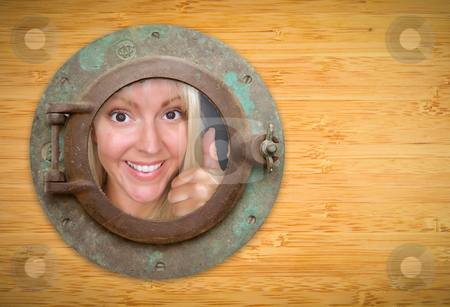 Antique Porthole on Bamboo Wall, Woman with Thumbs Up Looking stock photo, Antique Porthole on Bamboo Wall, Woman with Thumbs Up Looking Through Window. by Andy Dean
