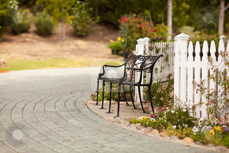Iron Park Bench near a White Picket Fence stock photo, Iron Park Bench near a White Picket Fence in a Rural Setting. by Andy Dean
