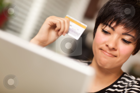 Smiling Multiethnic Woman Holding Credit Card Using Laptop stock photo, Smiling Multiethnic Woman Holding Credit Card While Using Laptop. by Andy Dean
