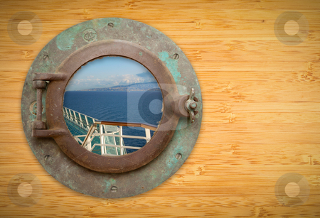 Antique Porthole on Bamboo Wall with View of Ship Deck Railing a stock photo, Antique Porthole on Bamboo Wall with View of Ship Deck Railing, Ocean, Land and Sky. by Andy Dean