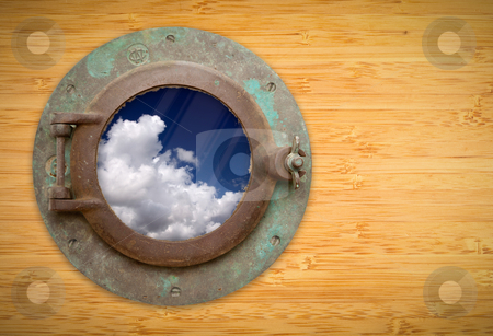 Antique Porthole on Bamboo Wall with View of Blue Sky and Clouds stock photo, Antique Porthole on Bamboo Wall with View of Beautiful Blue Sky and Clouds. by Andy Dean