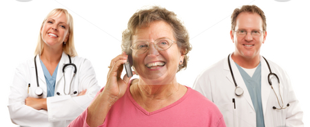 Happy Senior Woman Using Cell Phone and Doctors Behind stock photo, Happy Senior Woman Using Cell Phone with Male and Female Doctors or Nurses Behind Isolated on a White Background. by Andy Dean