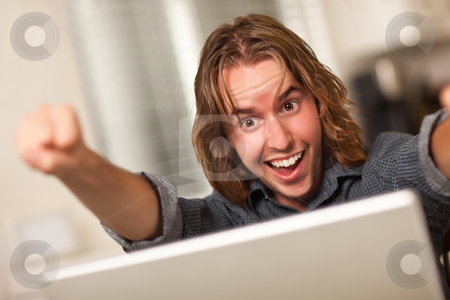 Cheering Young Man Using Laptop Computer stock photo, Happy, Cheering Young Man Using A Laptop Computer and Cheering with Fists in the Air. by Andy Dean