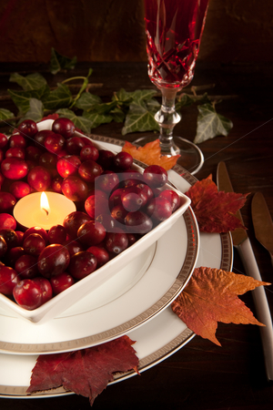 Thanksgiving dinner table stock photo, Thanksgiving dinner table closeup with cranberries and autumn leaves by Anneke