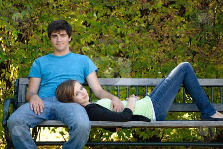 Relaxing Teenage Couple stock photo, A young teenage girl is lying on a bench with her head on her boyfriend's lap. by Richard Nelson