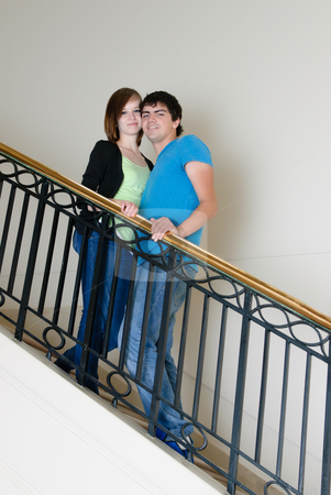 Teenage Couple Posing stock photo, A teenage couple posing on a staircase smiling. by Richard Nelson