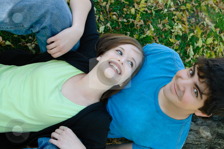 Relaxing Teen Couple stock photo, An top-down view of a teen couple lying on some leaves relaxing. by Richard Nelson