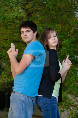 Fun Teens stock photo, Two teens having fun and pretending to hold guns while standing back to back. by Richard Nelson