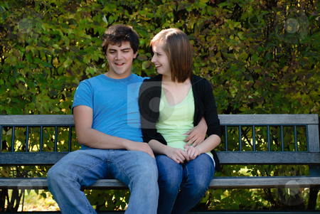 Two Teenagers On A Bench stock photo, Two teenagers snuggling and sitting on a park bench with leaves in the background. by Richard Nelson