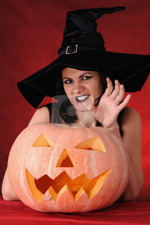 Witch stock photo, Young witch with a pumpkin on a red background by Salauyou Yury