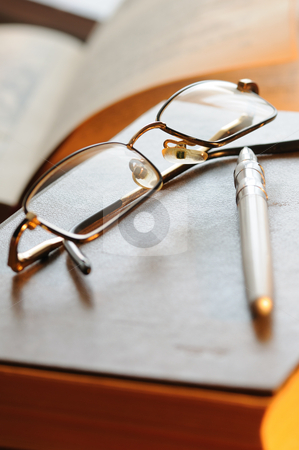 Glasses stock photo, Glasses and the pen lay on the old book by Salauyou Yury