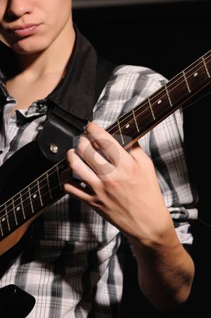 Guitarist stock photo, The guitarist plays on a guitar shooting closeup by Salauyou Yury