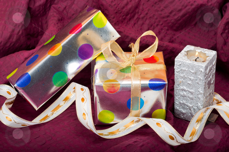 Christmas Still Life stock photo, Silver gift boxes with colorful dots and ribbons and candle on burgundy background by Timothy Hodgkinson