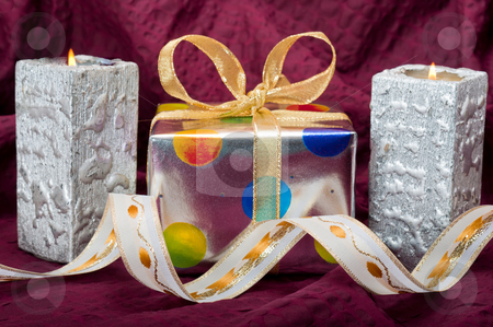 X-mas Still Life stock photo, Silver gitf box with silver candles and ribbons on burgundy background by Timothy Hodgkinson