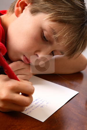 Boy writing note letter to santa stock photo, A boy at a table writing his wishlist for Santa for Christmas. by Leah-Anne Thompson
