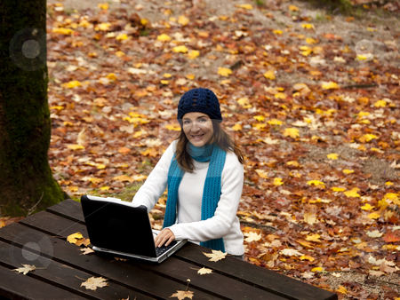 Outdoor work stock photo, Beautiful young woman in the park working with a laptop by ikostudio