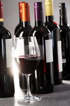 Wine stock photo, A glass of red wine and bottles in the background by Stocksnapper