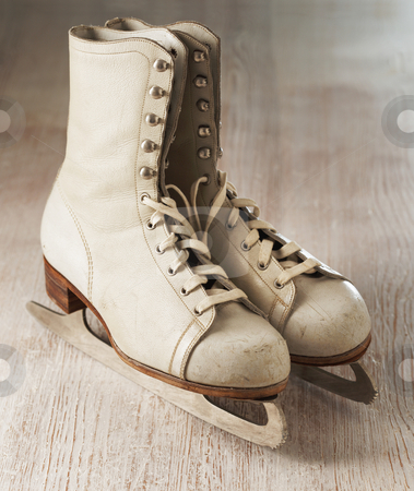 Old skates stock photo, Old white women's skates on wood by Stocksnapper
