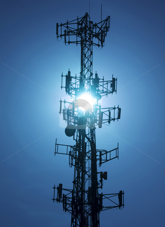 Cell phone tower stock photo, Cell phone tower back lit by the sun by Christian Delbert