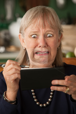 Senior woman with checkbook stock photo, Senior woman at home with checkbook by Scott Griessel