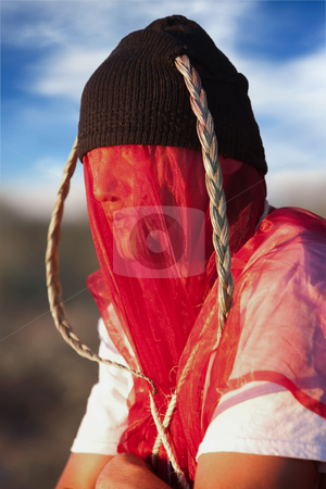 Man with strange headdress and veil stock photo, Man with strange headdress and red veil by Scott Griessel