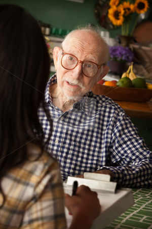 Elderly man in home with care provider or survey taker stock photo, Elderly man in home with care provider or survey taker in kitchen by Scott Griessel