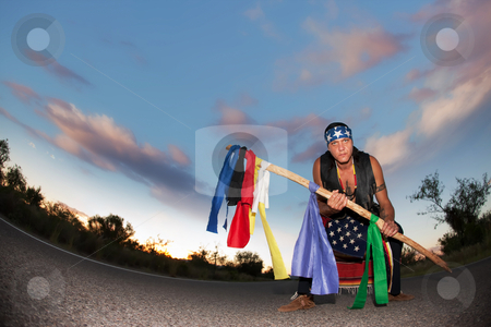 Indigenous man in the middle of a road with ceremonial pole and stock photo, Indigenous man squatting in the middle of a road with ceremonial pole and flags in the middle of a road with ceremonial pole representing seven directions by Scott Griessel