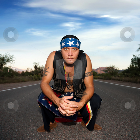 Indigenous man in the middle of a road stock photo, Indigenous man squatting in the middle of a road by Scott Griessel