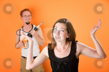 Frustrated woman and incompetent handyman stock photo, Frustrated woman with hands in there over her incompetent handyman by Scott Griessel