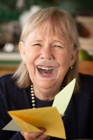 Senior woman with greeting card stock photo, Senior woman at home reading greeting card by Scott Griessel