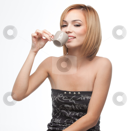Young woman having a sip of coffee stock photo, A side portrait of a young, blonde woman, having a sip of coffee from a cup she holds in one of her hands by dan comaniciu