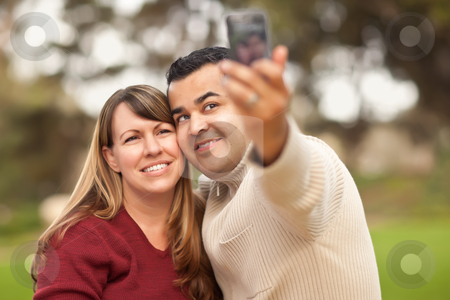 Attractive Mixed Race Couple Taking Self Portraits stock photo, Attractive Mixed Race Couple Taking Self Portraits in the Park. by Andy Dean