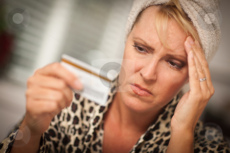 Upset Woman Holding Her Credit Card stock photo, Woman Obviously Very Upset Over Her Credit Card. by Andy Dean